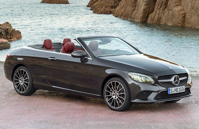 2019 Mercedes-Benz C-Class cabriolet exterior shot parked on a beach next to the ocean wading around rocks
