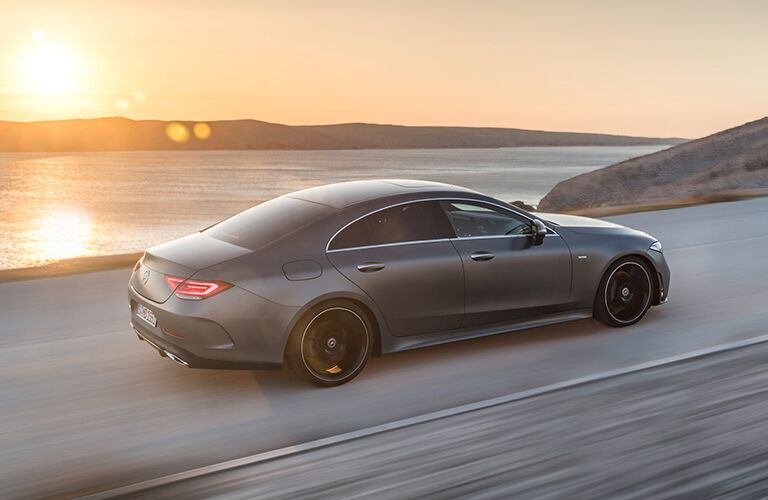 2019 Mercedes-Benz CLS exterior shot driving along the sea as a bright sun sets in the background