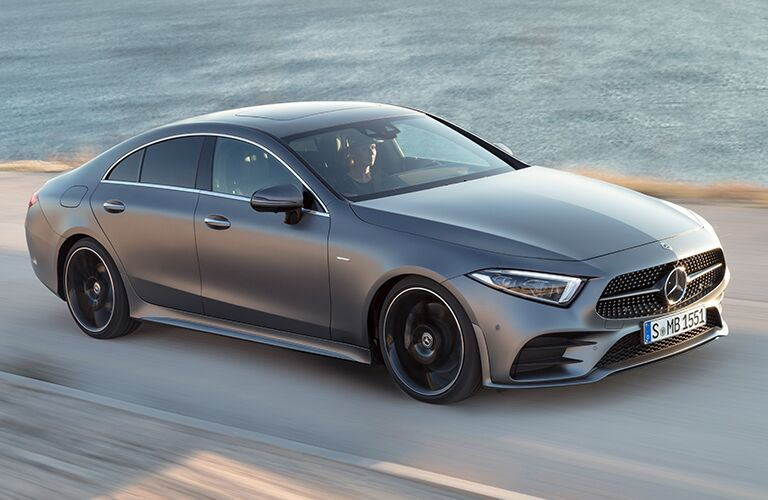 2019 Mercedes-Benz CLS exterior shot with gray paint job driving alongside gentle waves of the sea