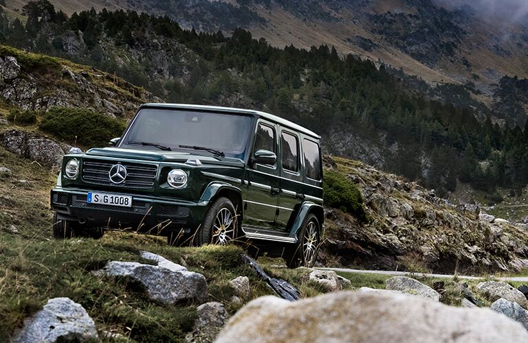 2019 Mercedes-Benz G-Class exterior shot driving through a mountain forest wilderness surrounded by rocks and trees