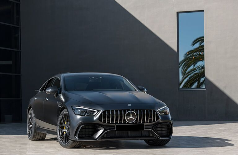 2019 Mercedes-AMG® GT 4-door coupe exterior front shot of black gray paint job parked in front of a beach house with a palm tree