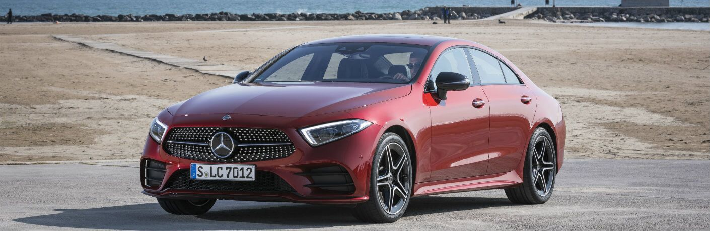 2019 Mercedes-Benz CLS 450 4MATIC exterior shot red paint parked near a beach, sea, and a fence of rocks and boulders