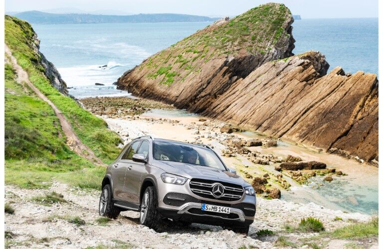 2020 Mercedes-Benz GLE SUV exterior shot of redesigned appearance as it travels over rocky terrain near the sea