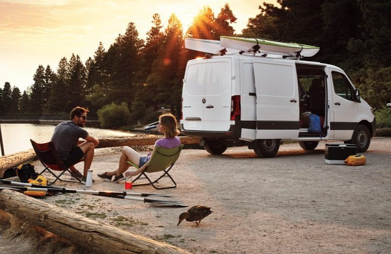 Couple sitting outside of 2020 Mercedes-Benz Sprinter van