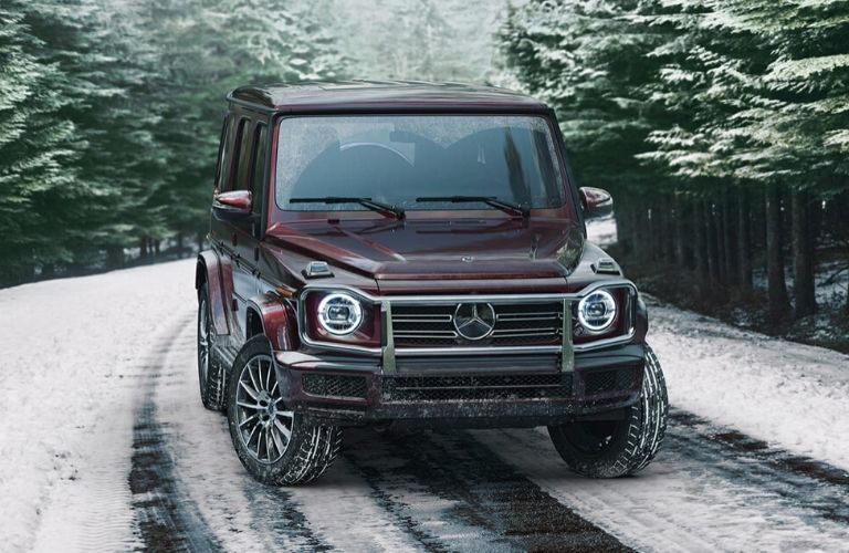Red 2020 Mercedes-Benz on a road with pine trees and snow from exterior front