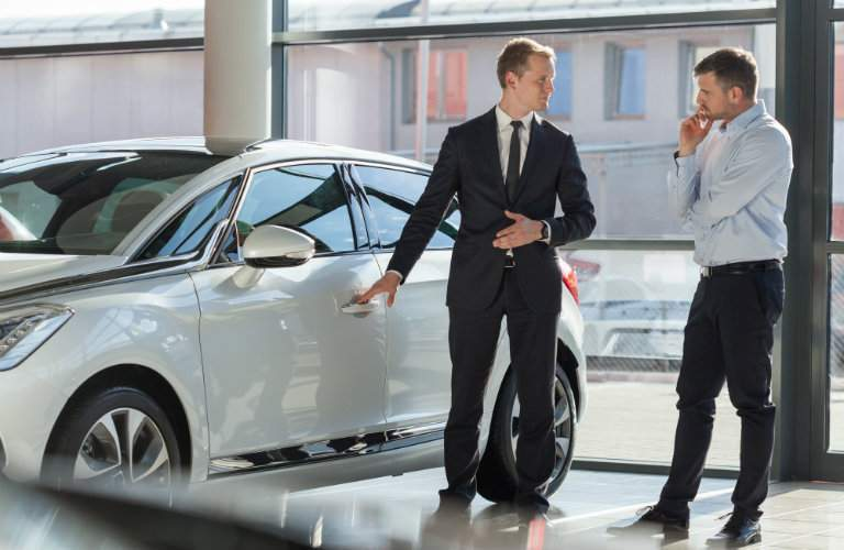 Salesman presenting vehicle to skeptical customer