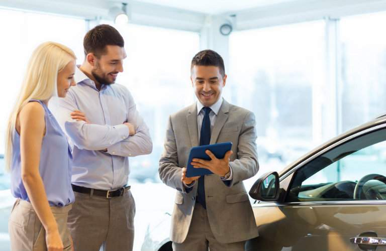 Salesman showing rates to couple shopping for a car