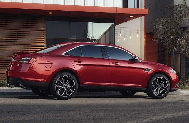 Red 2018 Ford Taurus Parked Next to a Modernistic House