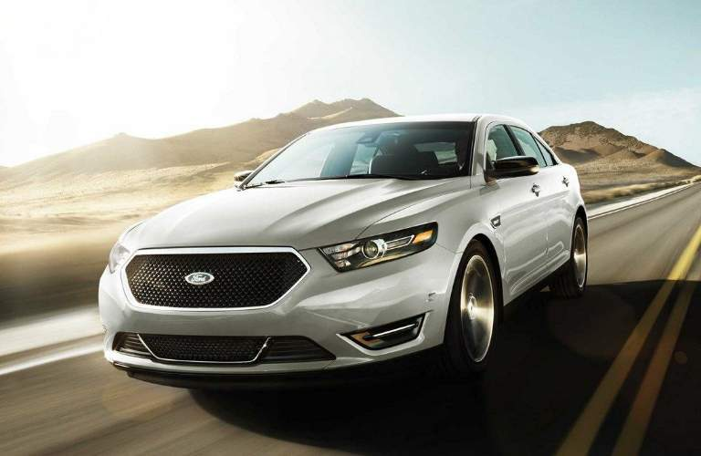 White 2018 Ford Taurus Driving Down a Highway with Mountains in the Background