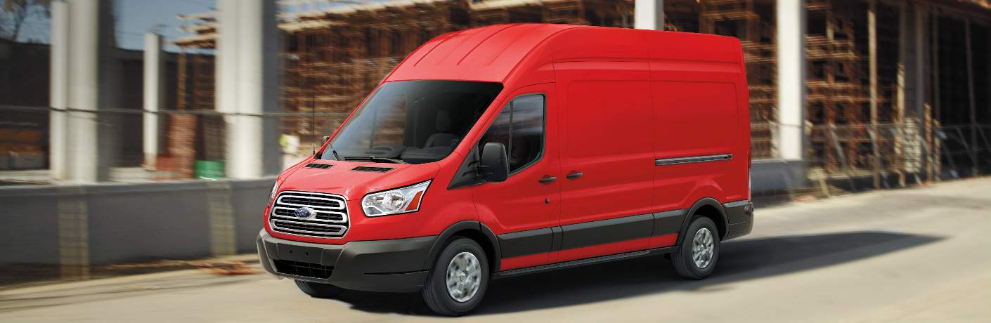 Red 2018 Ford Transit Cargo Van Driving by a Construction Site