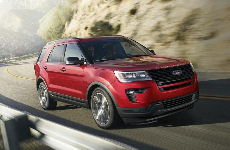 2019 Ford Explorer driving past a rocky cliff