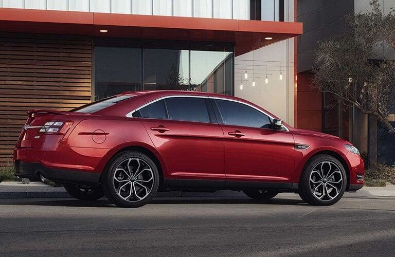 Red 2019 Ford Taurus parked by a building with wood paneling