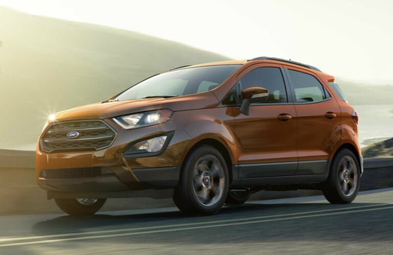 Orange 2019 Ford EcoSport Driving by a Lake