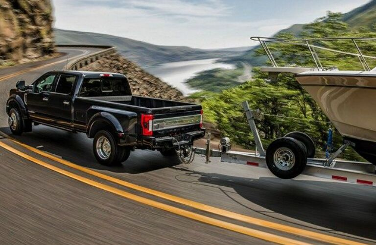 Black 2019 Ford F-250 Super Duty Towing a Boat on a Coastal Road