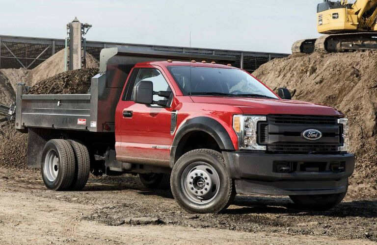 Red 2019 Ford F-Series Super Duty Chassis Cab with dirt in the pickup bed