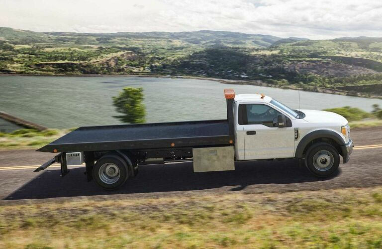 White 2019 Ford F-Series Super Duty Chassis Cab driving by a lake