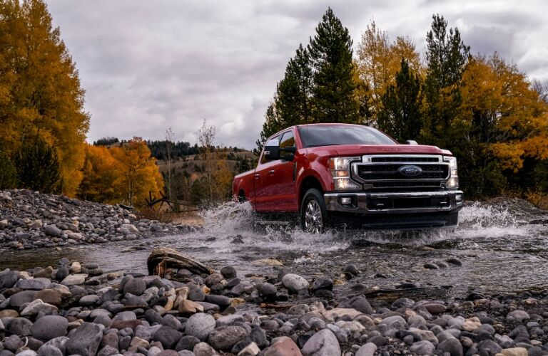 Red 2020 Ford F-Series Super Duty driving across a stream
