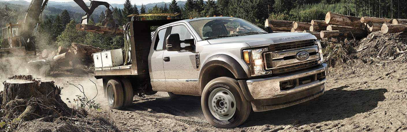 Silver 2018 Ford Super Duty Chassis Cab Driving through a Lumber Yard