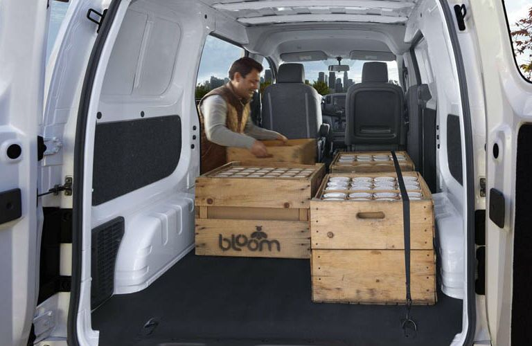 2018 Nissan NV200 Compact Cargo Van with rear doors open showing cargo area filled with crates