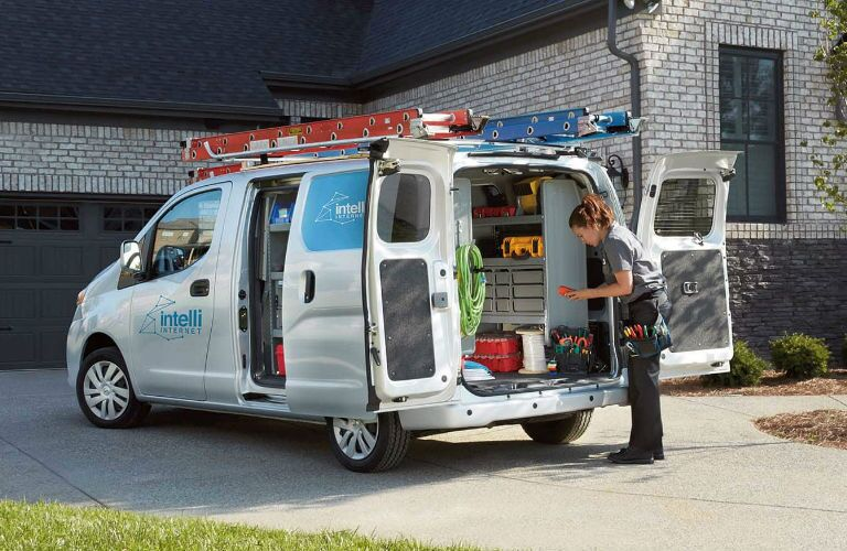 2019 Nissan NV200 Compact Cargo Van parked in a driveway with side and rear doors open