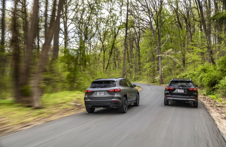 Two 2021 Mercedes-Benz GLA models driving down a forest road