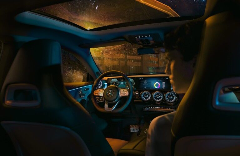 A photo of the driver's cockpit in the 2021 Mercedes-Benz CLA Coupe taken from the backseat.