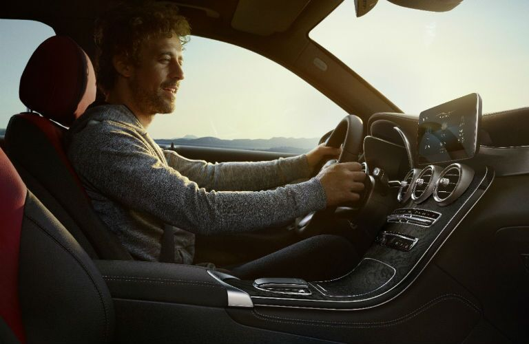 A photo of a person behind the wheel of a 2021 Mercedes-Benz GLC SUV.