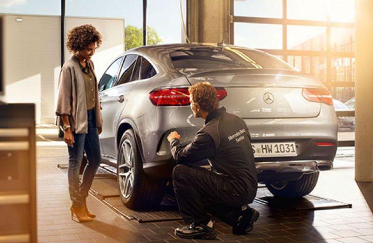 Mercedes-Benz technician servicing a Mercedes-Benz and talking to client