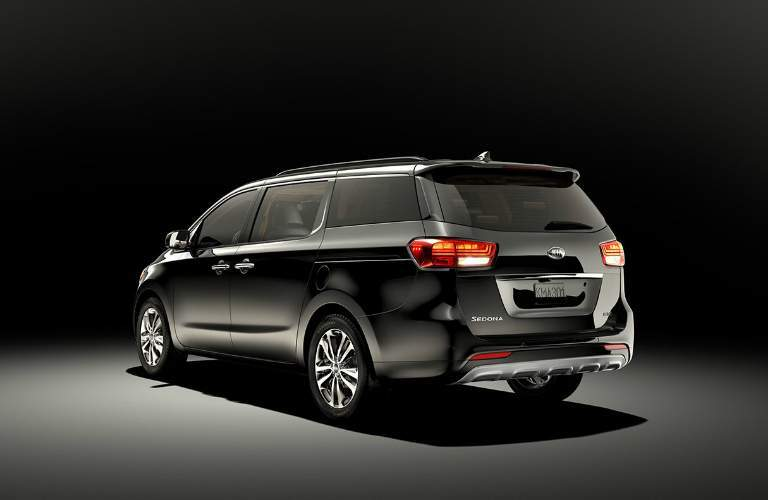 rear side view of a black 2018 Kia Sedona
