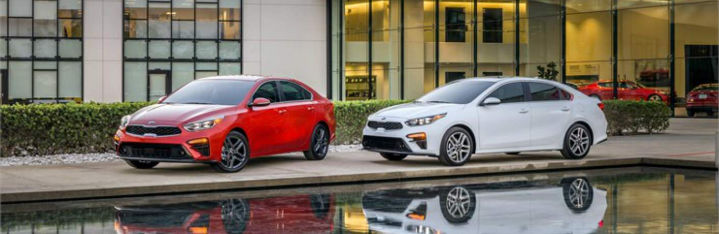 red and white 2019 Kia Forte models parked side by side