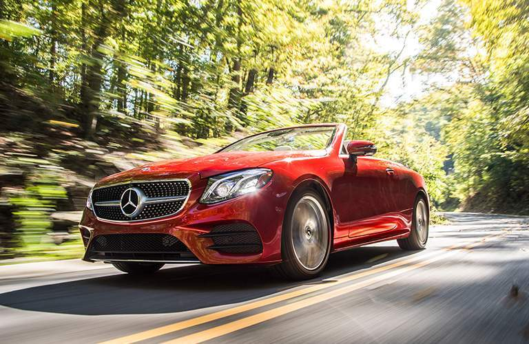 front view of a red 2018 Mercedes-Benz E-Class Cabriolet driving down a curved and wooded road