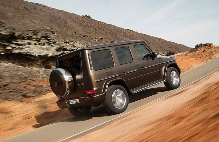 brown 2019 Mercedes-Benz G-Class driving on a road through scrubland