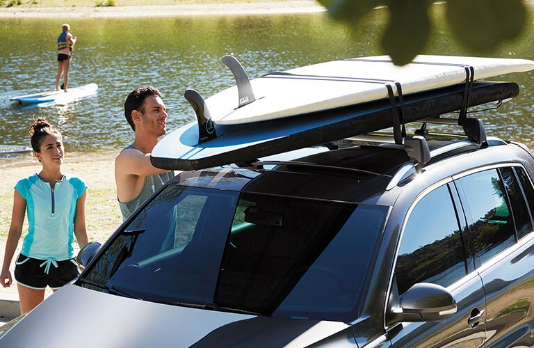 2016 Volkswagen Tiguan next to a lake with people loading cargo on roof rack