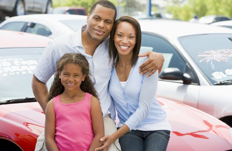 family of three sitting on the hood of a car