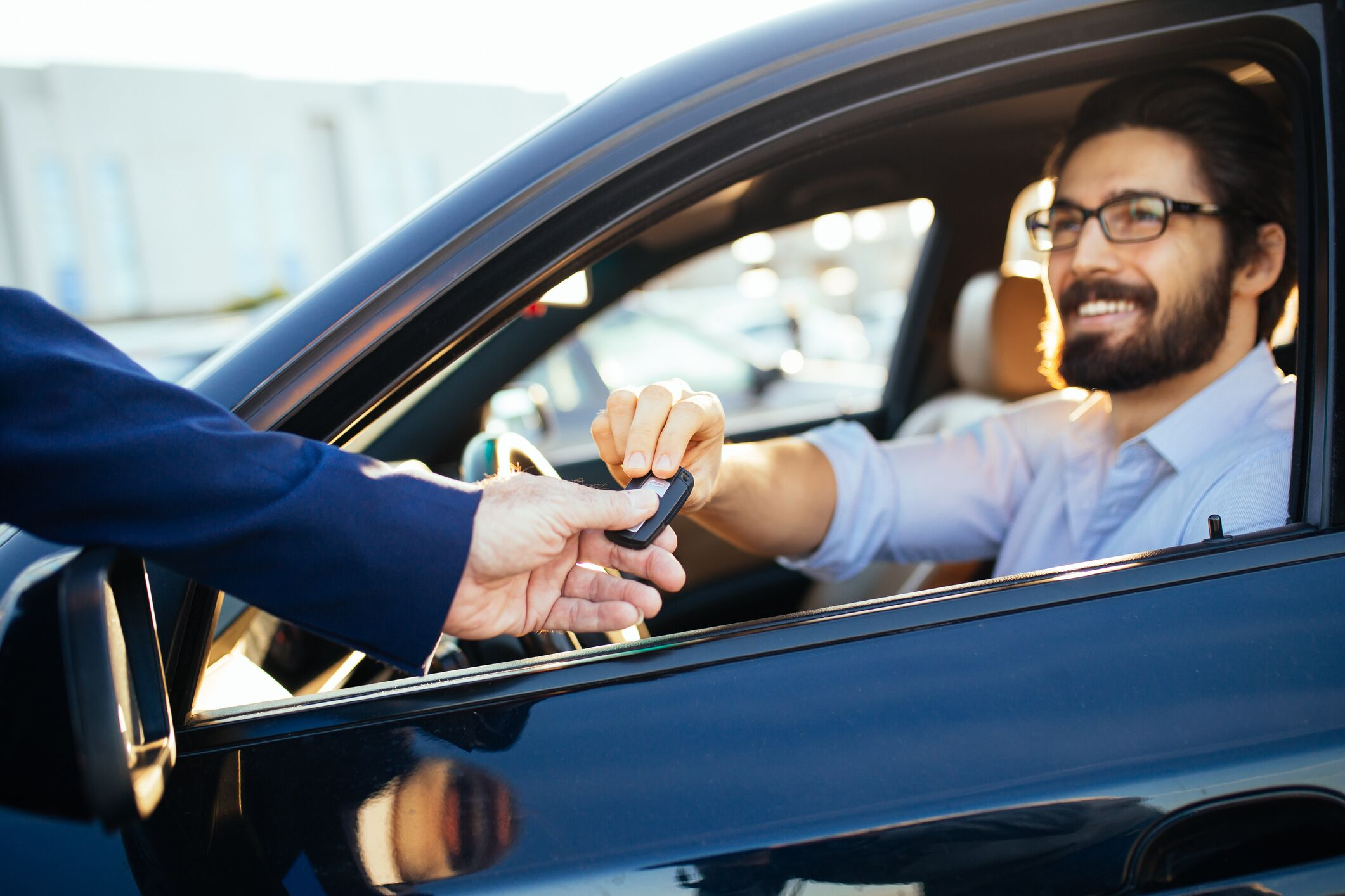 Salesman Handing Key to Driver in Car
