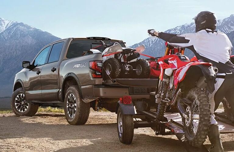 2020 Nissan TITAN with an ATV in the bed and a dirt bike on a trailer