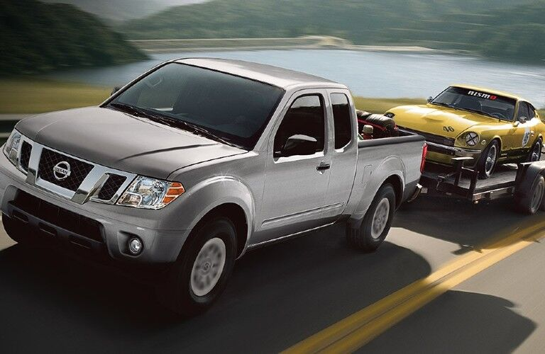 2021 Nissan Frontier towing a car on a trailer