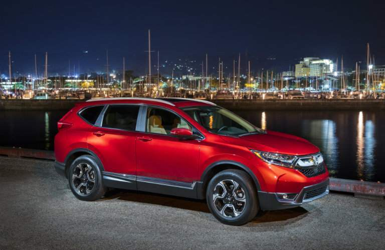 red 2018 Honda CR-V parked by the bay with city lights in the background