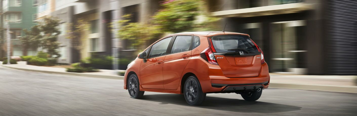 orange 2018 honda fit driving down urban road
