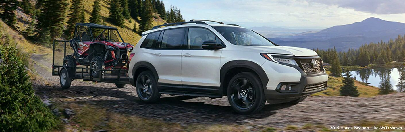 2019 Honda Passport Elite AWD towing a trailer with an ATV on it