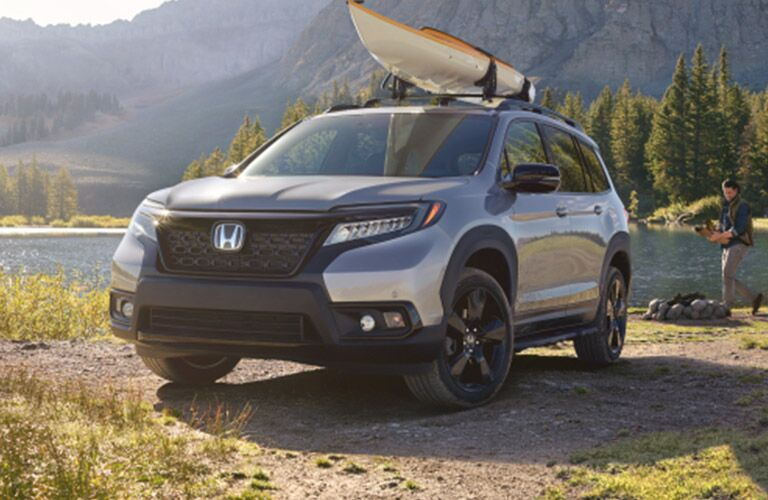 2019 Honda Passport parked by a lake with a canoe on top of it