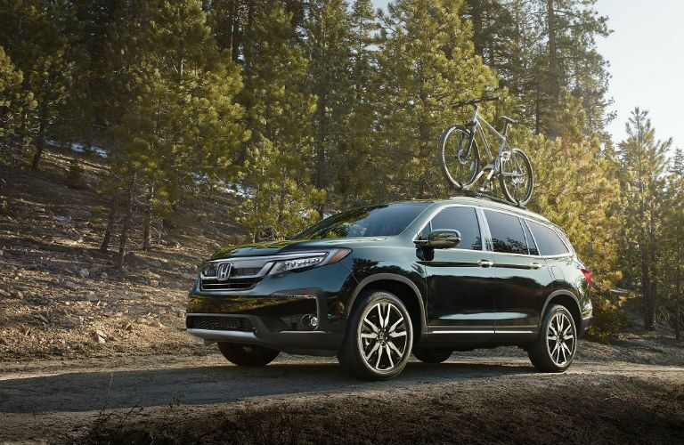 front of 2019 honda pilot in the woods with a bike on the roof