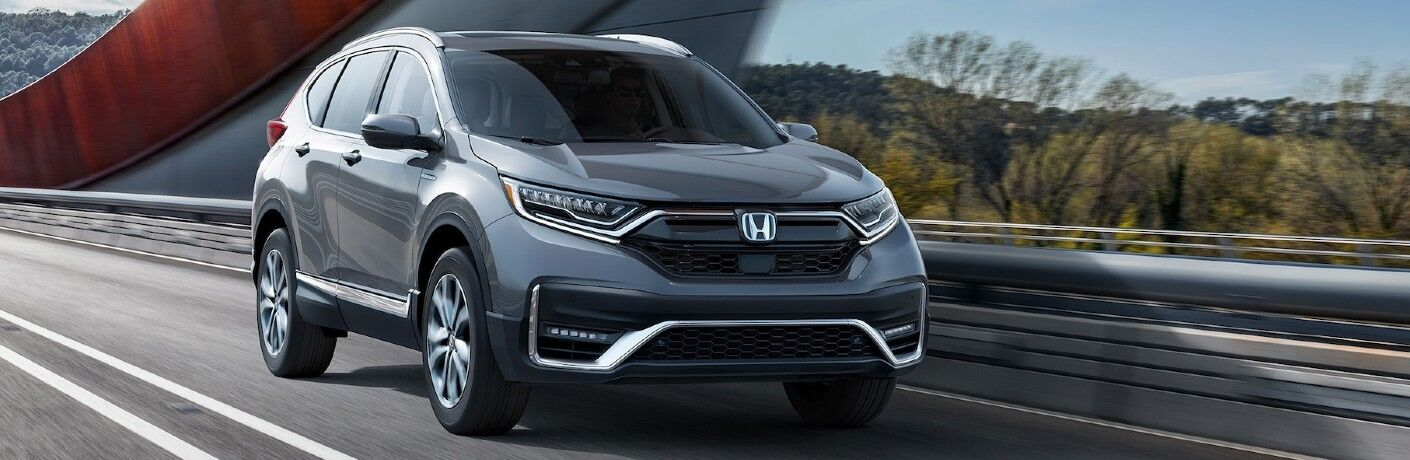 2020 Honda CR-V Hybrid Touring shown in Modern Steel Metallic driving on a road