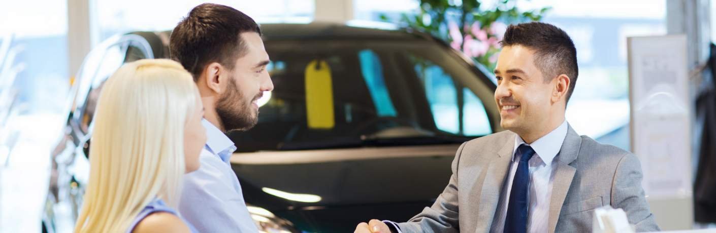 Couple Shaking Hands with a Car Salesman
