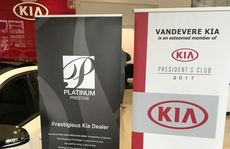 Kia VaDevere awards with white Kia Optima on left closeup