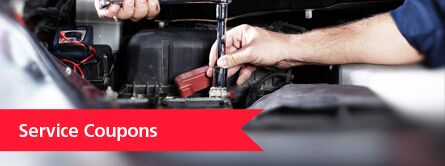 Service coupons with mechanic working on a car battery