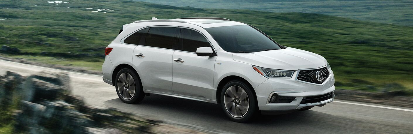 White 2019 Acura MDX driving on countryside road