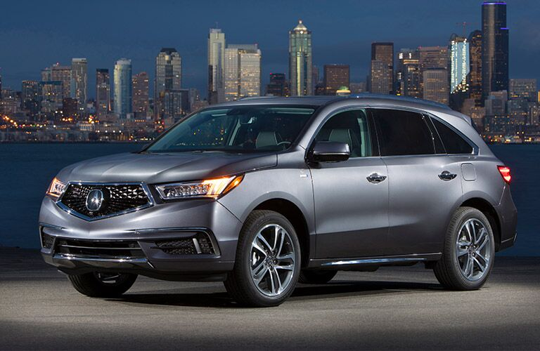 Silver 2019 Acura MDX parked with city skyline in background