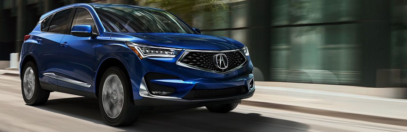 Blue 2019 Acura RDX driving with office building in view