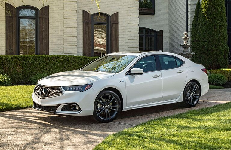 Profile view of white 2019 Acura TLX parked in front of modern house